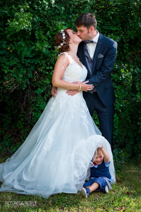Fotograf aus Dessau; Hochzeit, Brautleute küssen sich, Kind sitzt unter dem Kleid