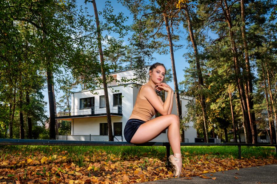 Balletttänzerin sitzt vor den Meisterhäusern in Dessau