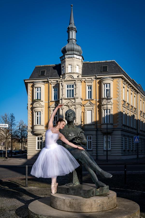 Balletttänzerin tanzt neben dem Denkmal von Kurt Weill in Dessau