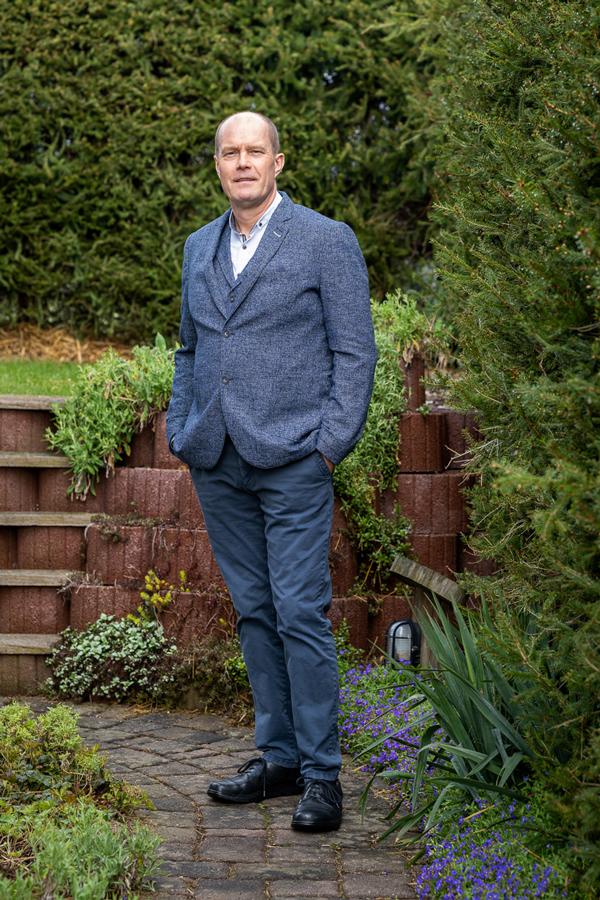 Mann steht in seinem Vorgarten