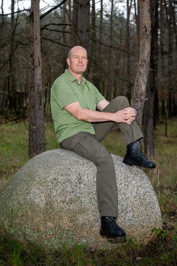 Mann sitzt auf einem Findling