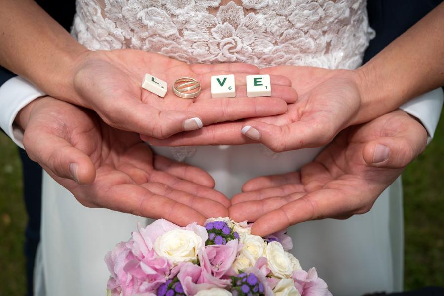 Love, Buchstaben auf den Händen eines Hochzeitspaares